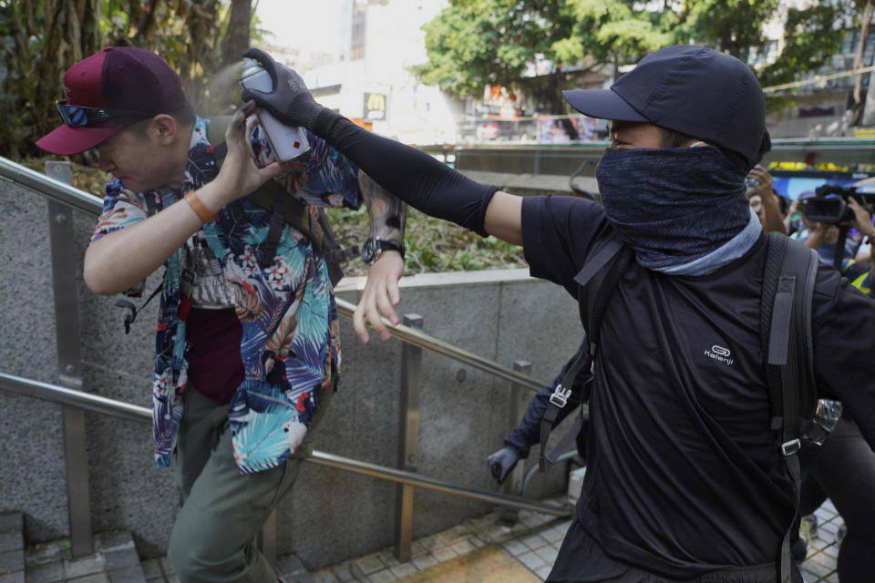 A protester sprays on a man who was trying to stop them for vandalizing near the Tsim She Tsui police station during a rally in Hong Kong, Sunday, Oct. 20, 2019. Hong Kong protesters again flooded streets on Sunday, ignoring a police ban on the rally and demanding the government meet their demands for accountability and political rights. (AP Photo/Vincent Yu)