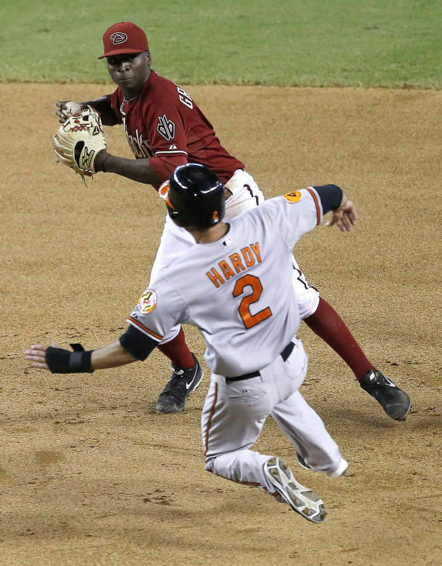 Arizona Diamondbacks' Didi Gregorius forces out Baltimore Orioles' J.J. Hardy (2) as he turns a double play on Nate McLouth during the 10th inning of a baseball game, Wednesday, Aug. 14, 2013, in Phoenix. (AP Photo/Matt York)