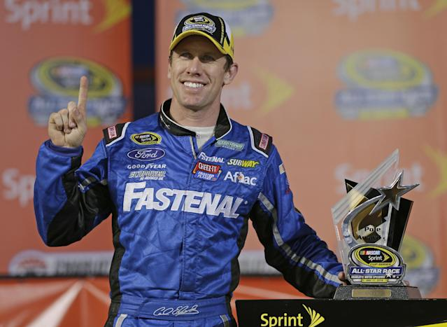 Carl Edwards poses with the trophy after winning the pole position for the NASCAR Sprint All-Star auto race at Charlotte Motor Speedway in Concord, N.C., Saturday, May 17, 2014. (AP Photo/Chuck Burton)