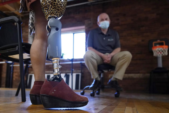 Claudine Humure, of Rwanda, takes a step with her new prosthetic leg as Arthur Graham, prosthetist at Next Step Bionics & Prosthetics, looks on, Monday, Sept. 20, 2021, in Newton, Mass. Humure was orphaned during her country's genocide and lost part of her leg to childhood cancer. Her new leg was provided free by the prosthetic clinic and features the latest in artificial limb technology. (AP Photo/Charles Krupa)