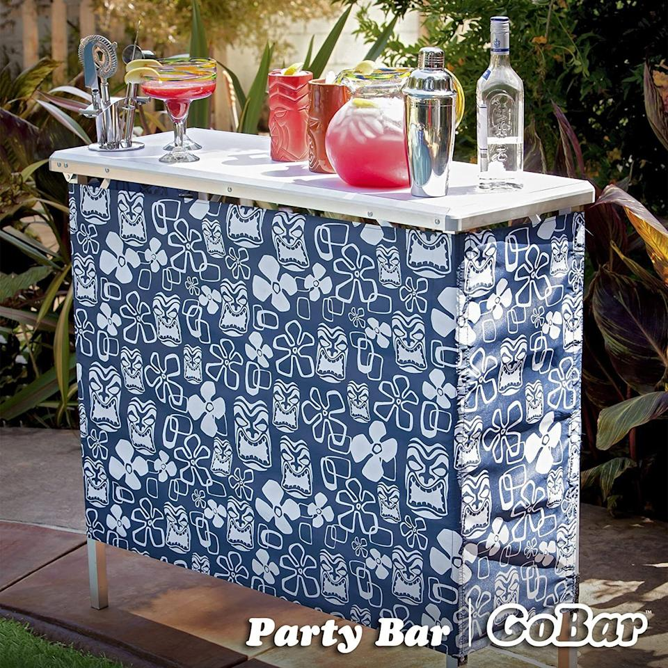 """You can safely store water, beer, soda and other cocktail-ready beverages *and* have the perfect corner for making drinks on your deck or patio.<br /><br /><strong>Promising review:</strong>""""Definitely a good buy!<strong>I love the portability and the storage shelf!</strong>The easy on/off covering provides an air of privacy. It sets up easy and holds its own! A very versatile year round serving & entertaining tool! I love the carry case that comes with it!"""" —<a href=""""https://amzn.to/3tNpO52"""" target=""""_blank"""" rel=""""nofollow noopener noreferrer"""" data-skimlinks-tracking=""""5580838"""" data-vars-affiliate=""""Amazon"""" data-vars-href=""""https://www.amazon.com/gp/customer-reviews/R37JOZN01DD0EL?tag=bfgenevieve-20&ascsubtag=5580838%2C8%2C33%2Cmobile_web%2C0%2C0%2C1159968"""" data-vars-keywords=""""cleaning"""" data-vars-link-id=""""1159968"""" data-vars-price="""""""" data-vars-product-id=""""16176769"""" data-vars-retailers=""""Amazon"""">Amazon Customer</a><br /><br /><strong>Get it from Amazon for<a href=""""https://amzn.to/3gxTgs0"""" target=""""_blank"""" rel=""""nofollow noopener noreferrer"""" data-skimlinks-tracking=""""5580838"""" data-vars-affiliate=""""Amazon"""" data-vars-asin=""""B005DD6ZIU"""" data-vars-href=""""https://www.amazon.com/dp/B005DD6ZIU?tag=bfgenevieve-20&ascsubtag=5580838%2C8%2C33%2Cmobile_web%2C0%2C0%2C1159982"""" data-vars-keywords=""""cleaning"""" data-vars-link-id=""""1159982"""" data-vars-price="""""""" data-vars-product-id=""""13026251"""" data-vars-product-img=""""https://m.media-amazon.com/images/I/41m4e1HyM+L.jpg"""" data-vars-product-title=""""GoPong GoBar Portable High Top Party Bar, Includes 3 Skirt Designs and Carrying Case - Great for Parties, Tailgating and Trade Shows"""" data-vars-retailers=""""Amazon"""">$64.99</a>.</strong>"""