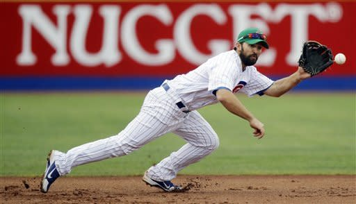 Chicago Cubs third baseman Blake DeWitt dives for a ground ball hit by Texas Rangers' Nelson Cruz in the second inning of a spring training baseball game, Saturday, March 17, 2012, in Las Vegas. DeWitt threw Cruz out at first on the play. The Rangers won 12-7. (AP Photo/Julie Jacobson)