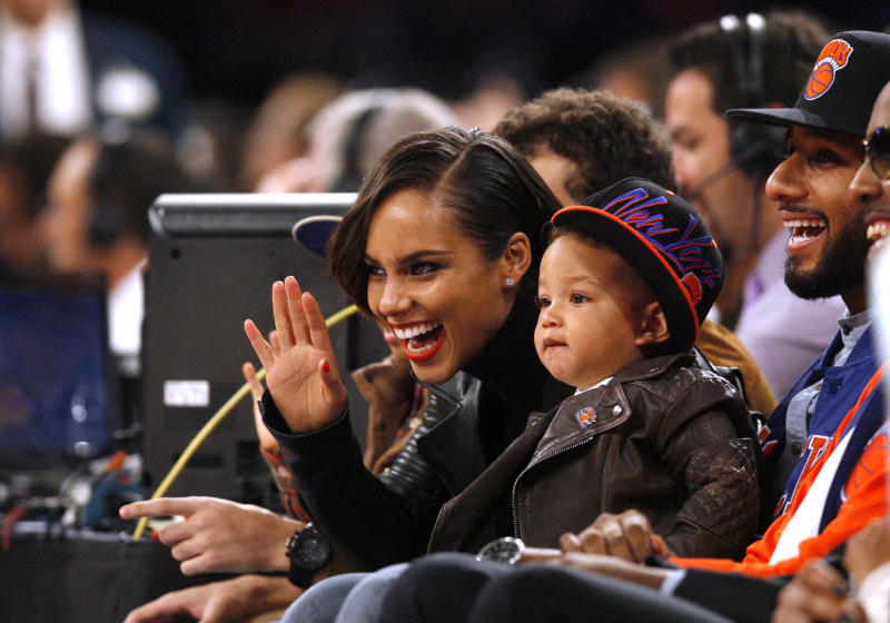 "FILE - In this Nov. 2, 2012 file photo, singer Alicia Keys, left, her son Egypt and her husband Swizz Beatz, right, watch courtside during an NBA basketball game between the New York Knicks and the Miami Heat, in New York. Keys is releasing her fifth album, ""Girl on Fire,"" on Nov. 27, 2012. It features Frank Ocean, Bruno Mars, Babyface, Emeli Sande, Maxwell, Nicki Minaj, John Legend, her husband Swizz Beatz and their son Egypt. (AP Photo/Jason DeCrow, File)"