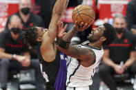 Brooklyn Nets' Kyrie Irving, right, goes up for a shot against the defense of Toronto Raptors' Khem Birch during the second half of an NBA basketball game Wednesday, April 21, 2021, in Tampa, Fla. (AP Photo/Mike Carlson)