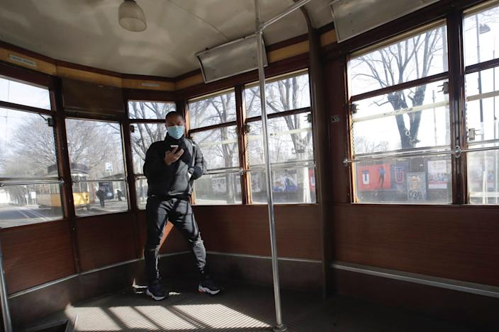 A man wearing a sanitary mask checks his phone as he takes a ride on a streetcar in Milan, Italy, Monday, Feb. 24, 2020.