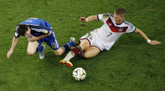 Germany's Bastian Schweinsteiger, right, tackles Argentina's Lionel Messi during the World Cup final soccer match between Germany and Argentina at the Maracana Stadium in Rio de Janeiro, Brazil, Sunday, July 13, 2014. Mario Goetze volleyed in the winning goal in extra time to give Germany its fourth World Cup title with a 1-0 victory over Argentina on Sunday. (AP Photo/Fabrizio Bensch, Pool)