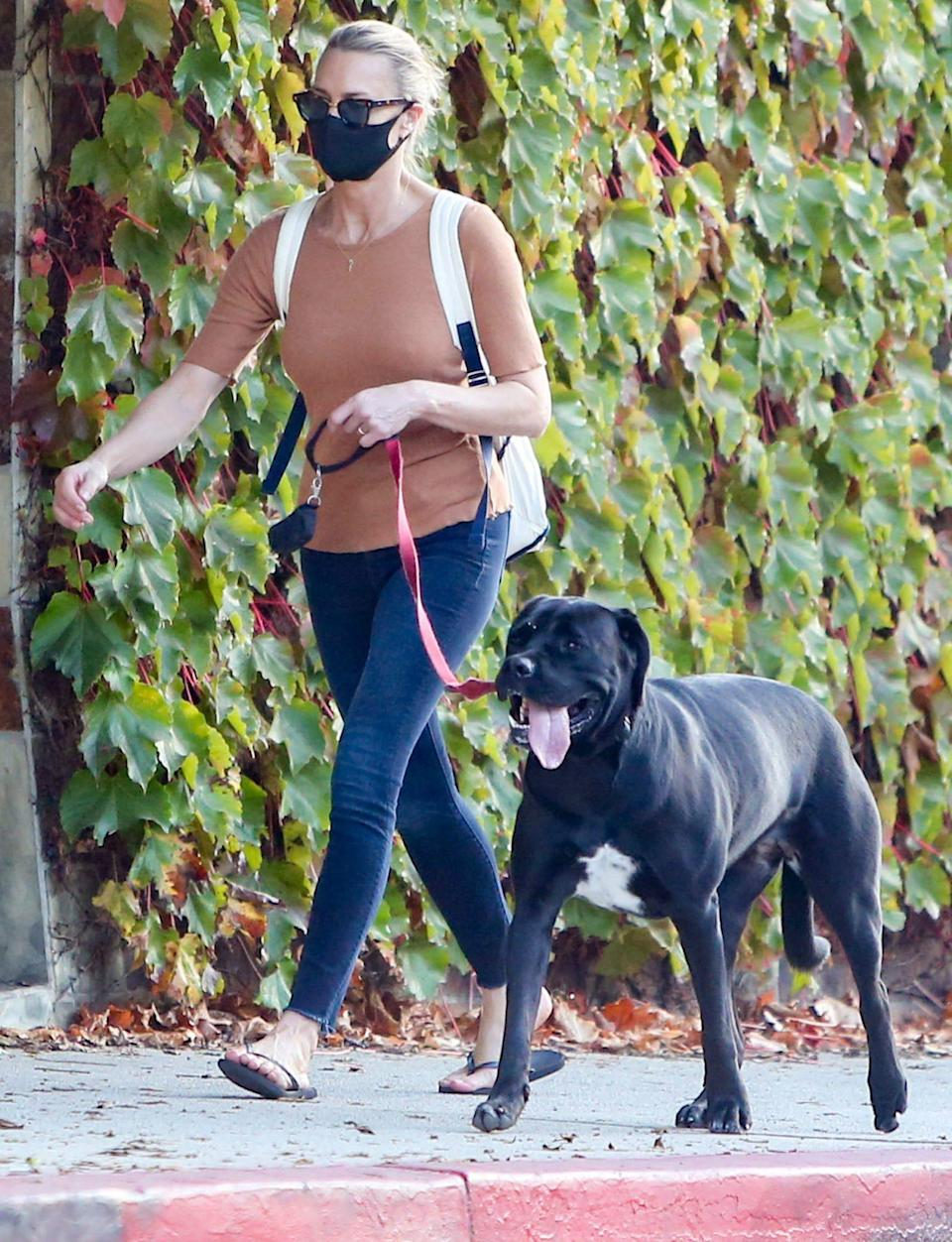 <p>Robin Wright goes for a walk with her dog on Monday in L.A., sporting a mask and backpack. </p>