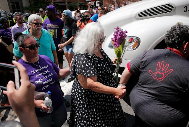 <p>Susan Bro (C), mother of Heather Heyer, arrives at a makeshift memorial for her daughter Heather who was killed one year ago during a deadly clash, August 12, 2018 in Charlottesville, Virginia. Charlottesville has been declared in a state of emergency by Virginia Gov. Ralph Northam as the city braces for the one year anniversary of the deadly clash between white supremacist forces and counter protesters over the potential removal of Confederate statues of Robert E. Lee and Jackson. A 'Unite the Right' rally featuring some of the same groups is planned for today in Washington, DC. (Photo: Win McNamee/Getty Images) </p>