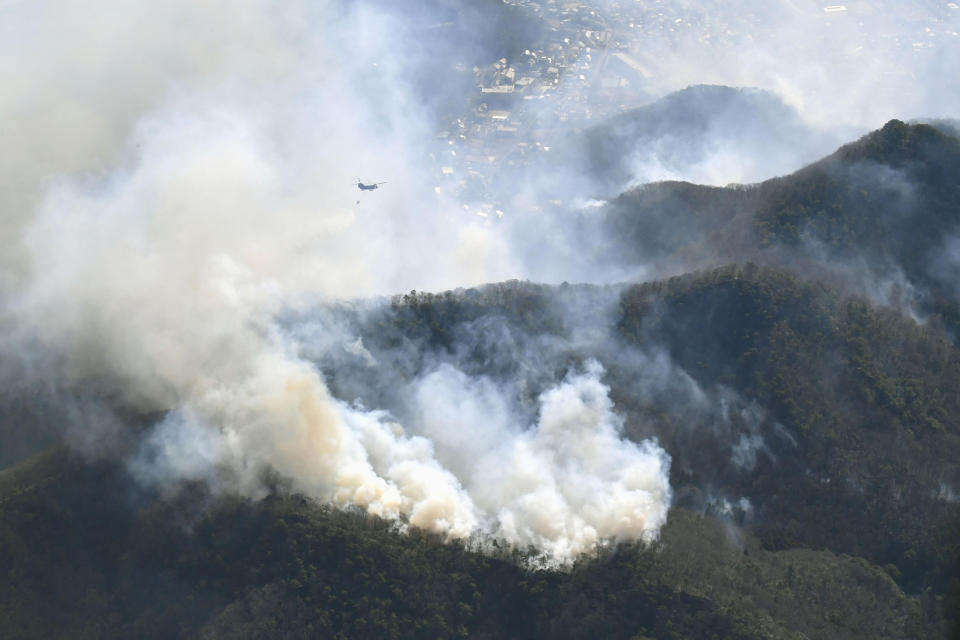 A helicopter dumps water on a wildfire in Ashikaga, Tochigi prefecture, north of Tokyo Wednesday, Feb. 24, 2021. A forest fire broke out in the rural area Thursday, near another blaze burning since Sunday, Feb. 21. (Kyodo News via AP)