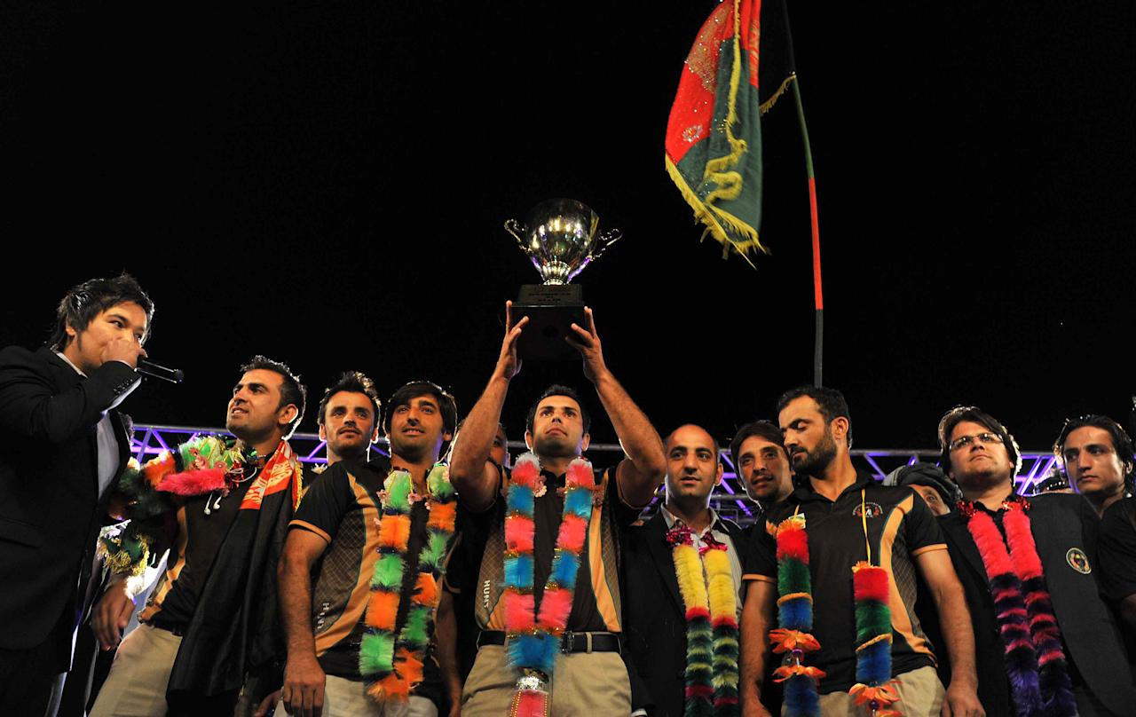 Afghan cricket team captain Mohammad Nabi (C), poses with the ACC Cup after the team arrived in Kabul on October 12, 2013. Afghanistan's cricket team received a heroes' welcome as cheering crowds lined the streets and packed a stadium in Kabul to greet the players after they qualified for the 2015 World Cup. AFP PHOTO/ Noorullah SHIRZADA        (Photo credit should read Noorullah Shirzada/AFP/Getty Images)