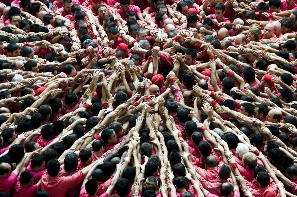 TARRAGONA, SPAIN - OCTOBER 07:  Members of the Colla 'Vella de Valls' start a construction of a human tower during the 24th Tarragona Castells Comptetion on October 7, 2012 in Tarragona, Spain. The 'Castellers' who build the human towers with precise techniques compete in groups, known as 'colles', at local festivals with aim to build the highest and most complex human tower. The Catalan tradition is believed to have originated from human towers built at the end of the 18th century by dance groups and is part of the Catalan culture.  (Photo by David Ramos/Getty Images)