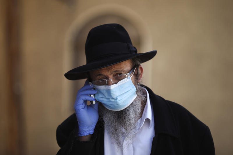 An Ultra-Orthodox Jewish man wears a protective face mask on a mainly deserted street because of the government's measures to help stop the spread of the coronavirus, in Bnei Brak, a suburb of Tel Aviv, Israel, Friday, April 3, 2020. By Friday, Bnei Brak had become the country's worst hot spot and now resembles a ghost town. (AP Photo/Oded Balilty)
