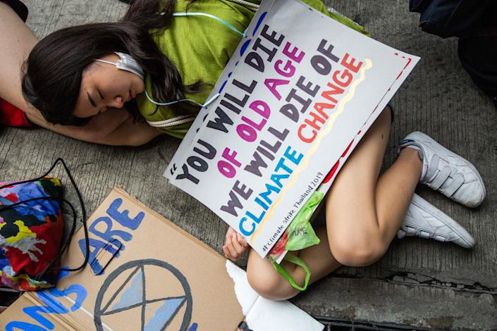 """Thai people take part in a """"die-in"""", where strikers lie on the ground and pretend to die, symbolising the impact of climate change in front of the Ministry of Natural Resources and Environment on September 20, 2019 in Bangkok, Thailand. (Photo: Lauren DeCicca/Getty Images)"""