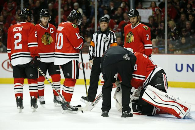 Chicago Blackhawks goalie Corey Crawford, right, is tended to after suffering an injury during the first period of an NHL hockey game against the Florida Panthers on Sunday, Dec. 8, 2013, in Chicago, Ill. (AP Photo/Andrew A. Nelles)