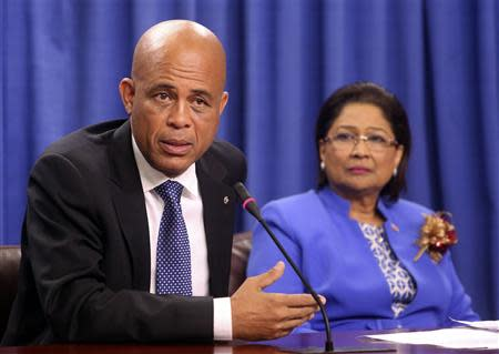 Haitian President Michel Martelly addresses a media conference, as Trinidad and Tobago's Prime Minister and chairperson of the Caribbean Community (CARICOM) Kamla Persad-Bissessar looks on, at the Diplomatic Centre in St Ann's, on the outskirts of the capital Port-of-Spain, November 26, 2013. REUTERS/Andrea De Silva