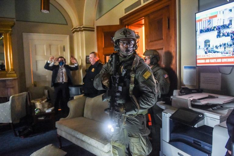 A Congress staffer holds his hands up while Capitol Police Swat team check everyone in the room as they secure the floor of Trump supporters in Washington, DC