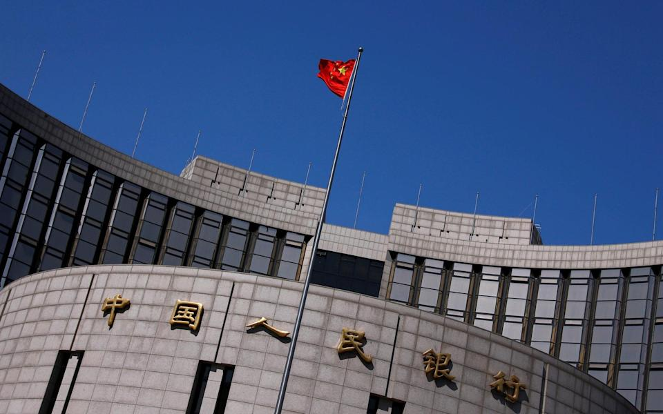 A Chinese flag flutters outside the headquarters of the country's central bank in Beijing - Petar Kudjundzic/REUTERS