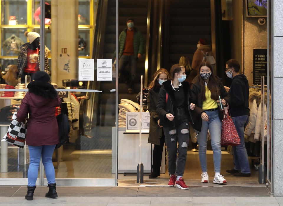 People leave a store in Prague, Czech Republic, Thursday, Dec. 3, 2020. A sign of normalcy has returned to the Czech Republic ahead of the Christmas period after the government eased some of its most restrictive measures imposed to contain the recent massive surge of coronavirus infections. On Thursday all stores, shopping malls, restaurants, bars and hotels were allowed to reopen. (AP Photo/Petr David Josek)