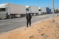 A man walks past trucks near the border in Guerguerat, located in the Western Sahara, in November 2020