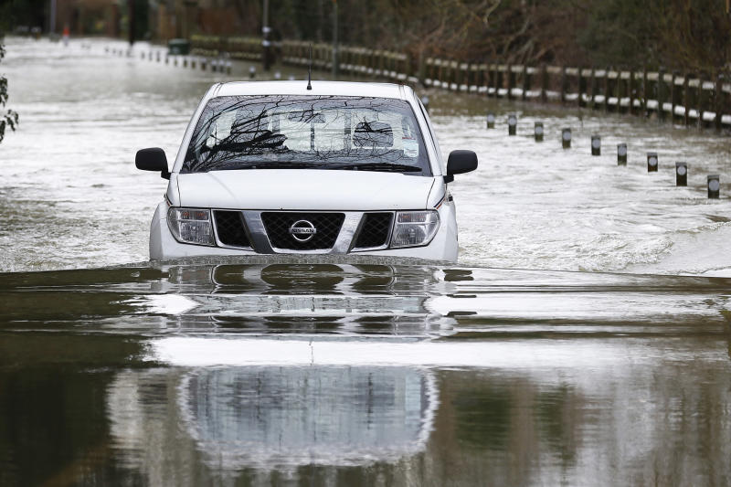 A car drives through a flooded road in Shepperton, England, Tuesday, Feb. 11, 2014. The River Thames has burst its banks after reaching its highest level in years, flooding riverside towns upstream of London. The River Thames has burst its banks after reaching its highest level in years, flooding riverside towns upstream of London. Residents and British troops piled up sandbags to protect properties from the latest bout of flooding, but the river overwhelmed their defenses in several places Monday, leaving areas underwater. (AP Photo/Sang Tan)