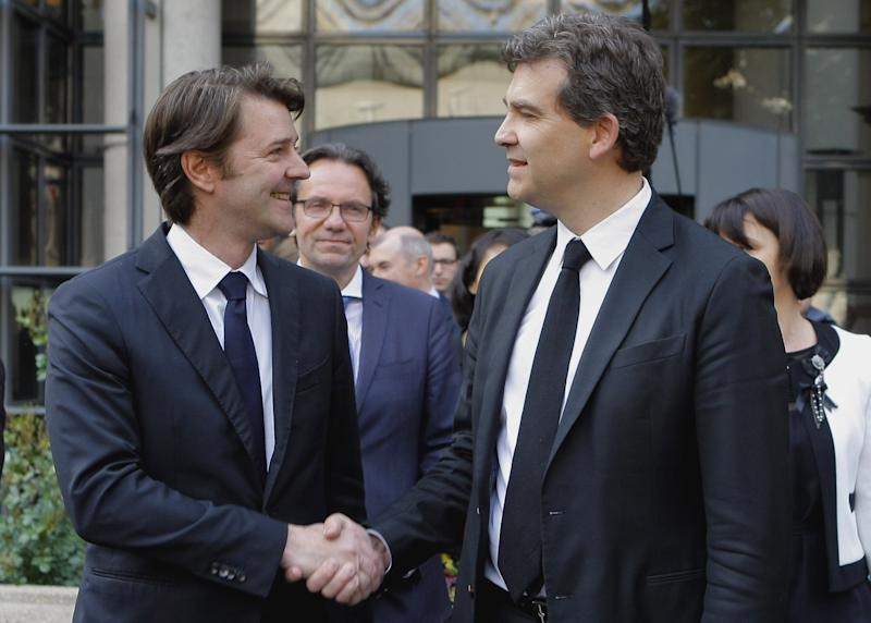 Newly appointed French Industrial Recovery Minister Arnaud Montebourg, right, shakes hands with outgoing French Economy and Finance Minister Francois Baroin, during their handover ceremony Thursday May 17, 2012 at the Bercy ministry in Paris.(AP Photo/Jacques Brinon)