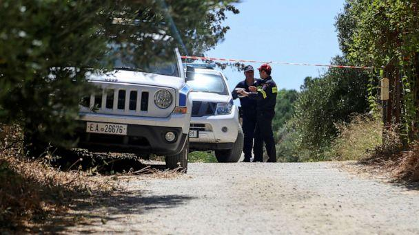 PHOTO: A police officer and a member of a fire brigade search and rescue team stand behind a police cordon, in an area where the body of a woman was found, near the village of Kolimpari on the island of Crete, Greece, July 9, 2019. (Makis Kartsonakis/Reuters)