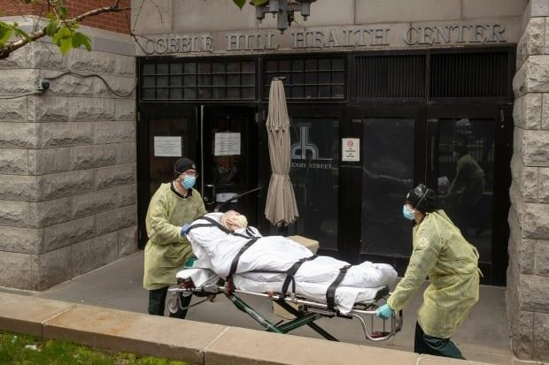 Emergency medical technicians wheel a patient out of the Cobble Hill Health Center in New York in April. A report from the New York State Attorney General says the state government undercounted deaths in nursing homes by as much as 50 per cent.