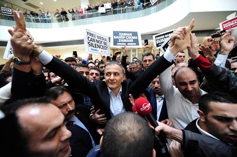 Ekrem Dumanli (C), editor-in-chief of Zaman newspaper, waves to staff members while being arrested by counter-terror police at the newspaper's headquarters in Istanbul on December 14, 2014 (AFP Photo/Ozan Kose)