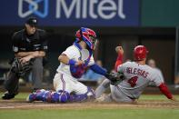 Home plate umpire Nic Lentz, left, looks on as Texas Rangers catcher Jose Trevino, center, tags out Los Angeles Angels' Jose Iglesias (4) who was trying to score on a Brandon Marsh double in the sixth inning of a baseball game in Arlington, Texas, Tuesday, Aug. 3, 2021. (AP Photo/Tony Gutierrez)