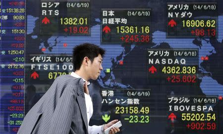 A pedestrian holding his mobile phone walks past an electronic board showing the stock market indices of various countries outside a brokerage in Tokyo June 19, 2014. REUTERS/Yuya Shino