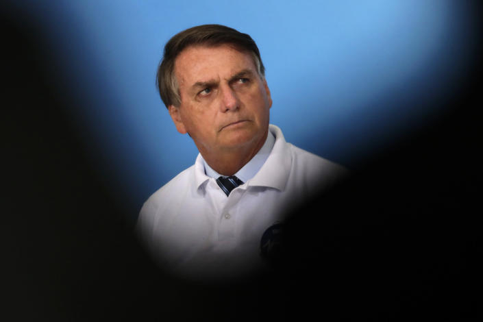 FILE - In this Jan. 12, 2021 file photo, Brazil's President Jair Bolsonaro attends a ceremony at the Planalto presidential palace in Brasilia, Brazil. Experts have blamed the president, a far-right former army captain, for fueling anti-vaccine sentiment in Brazil, compromising the mass immunization effort. (AP Photo/Eraldo Peres, File)