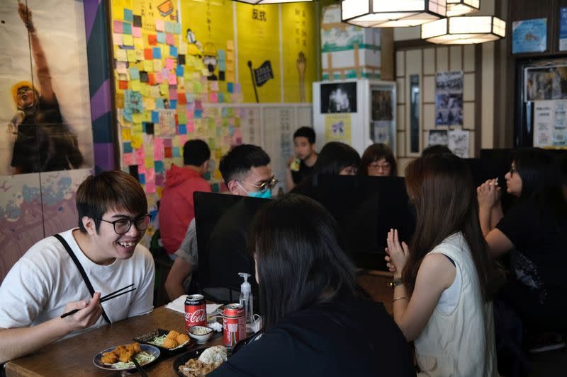 Customers sit inside a yellow restaurant called ''Mainichi'', during ''golden ween'' holiday by supporting local businesses with the pro-democracy views, in Hong Kong
