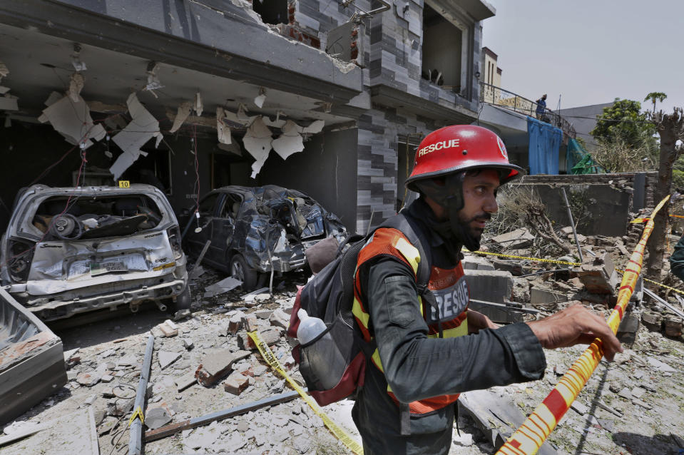 A rescue worker examine the site of explosion in Lahore, Pakistan, Wednesday, June 23, 2021. A powerful explosion ripped through a residential area in the eastern city of Lahore on Wednesday, killing few people and injuring some others, police and rescue officials said. (AP Photo/K.M. Chaudary)