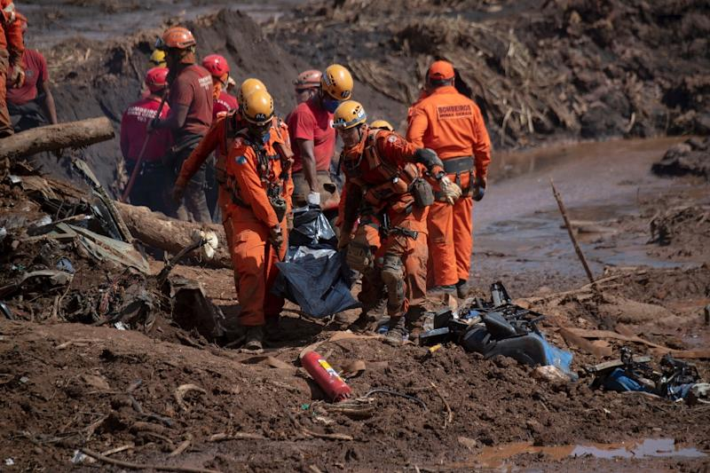 The task of recovering the bodies of people killed in the collapse of a dam in Brazil requires men digging down, often by hand, into mud up to 15 meters (50 feet) deep, pulling out corpses that are bagged then airlifted away by helicopter (AFP Photo/Mauro PIMENTEL)