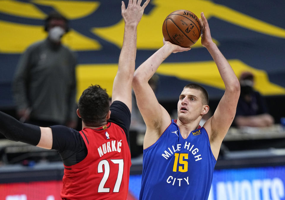 Denver Nuggets center Nikola Jokic (15) shoots against Portland Trail Blazers center Jusuf Nurkic (27) during the first half of Game 5 of a first-round NBA basketball playoff series Tuesday, June 1, 2021, in Denver. (AP Photo/Jack Dempsey)