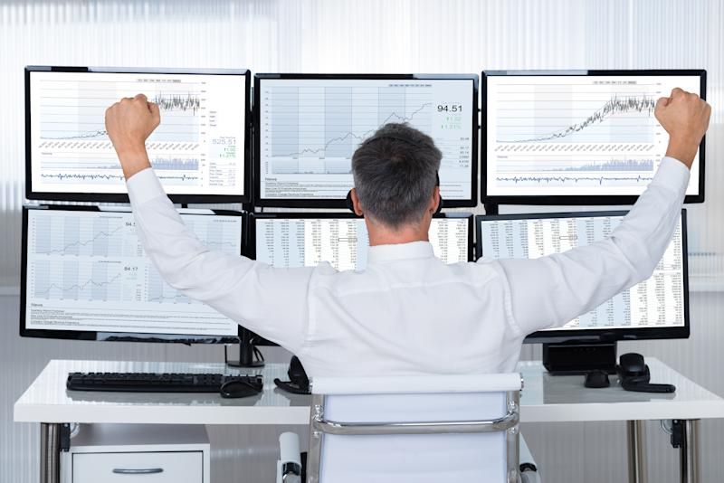 A businessman in front of six computer monitors showing charts and graphs, celebrating
