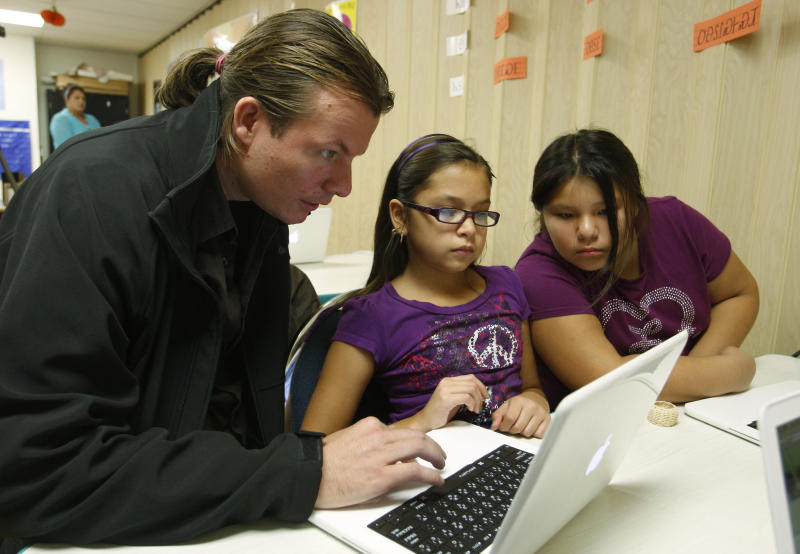 FILE - In this file photo taken Monday, Oct. 25, 2010, Joseph Erb, helps out students Cambria Bird, left, and Lauren Grayson, right, in the fifth grade class of the Cherokee Nation Immersion School in Tahlequah, Okla., Cherokee children are asking for iPods and iPhones for Christmas this year, and their parents are having a much tougher time saying no than one might expect. Nearly two centuries after a Cherokee silversmith named Sequoyah developed a system of symbols for each syllable spoken by the Cherokee, the tribe's written language has become available on iPhone and iPods. (AP Photo/Sue Ogrocki, File)