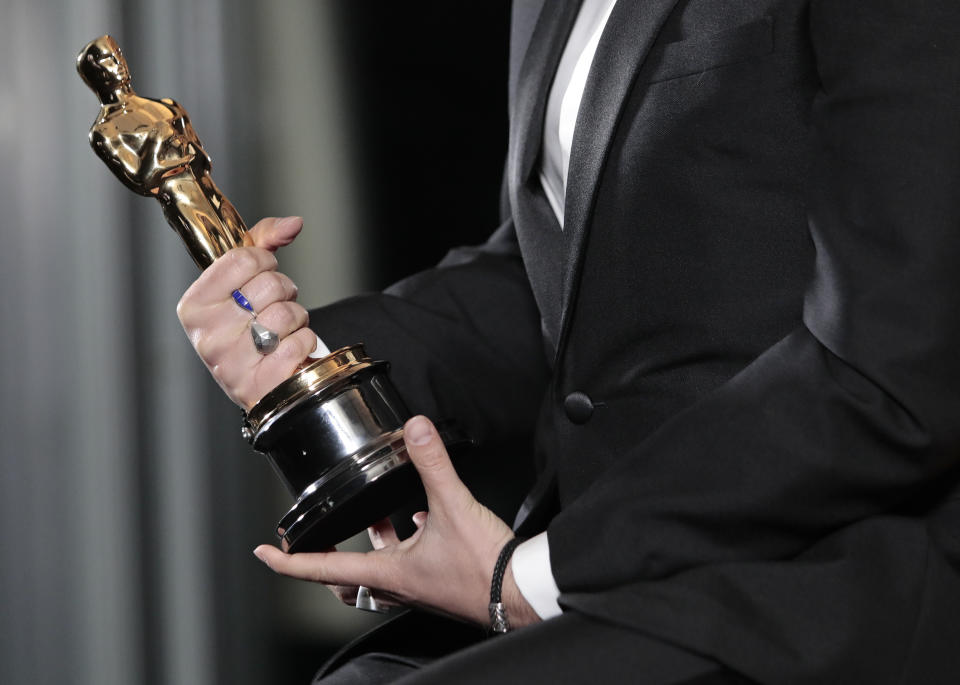 Florian Zeller holds his Oscars statuette after winning the Best Adapted Screenplay for the 'The Father' at a screening of the Oscars on Monday April 26, 2021 in Paris, France. (AP Photo/Lewis Joly, Pool)