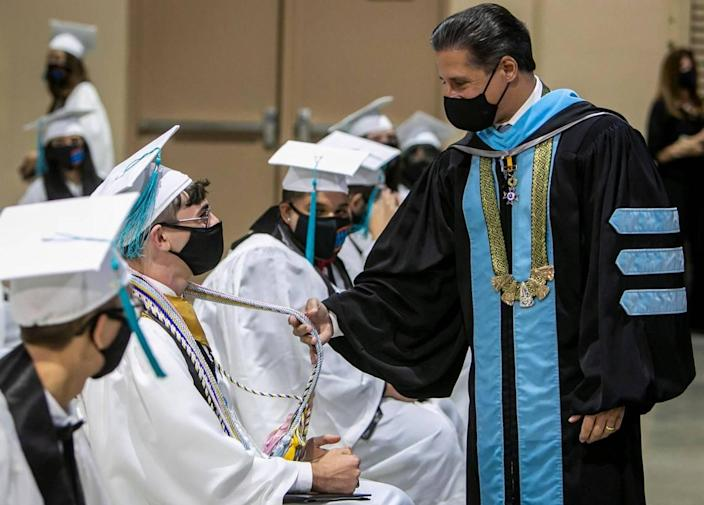 Miami-Dade County Schools Superintendent Alberto Carvalho (right) asks graduate Justin Perez (sitting, second from left) if he needs any more honors during the graduation ceremony for students of Miami Arts Studio 6-12 @ Zelda Glazer at the Miami-Dade Fair and Expo. Miami-Dade Public Schools began its high school graduations on Tuesday, June 1.