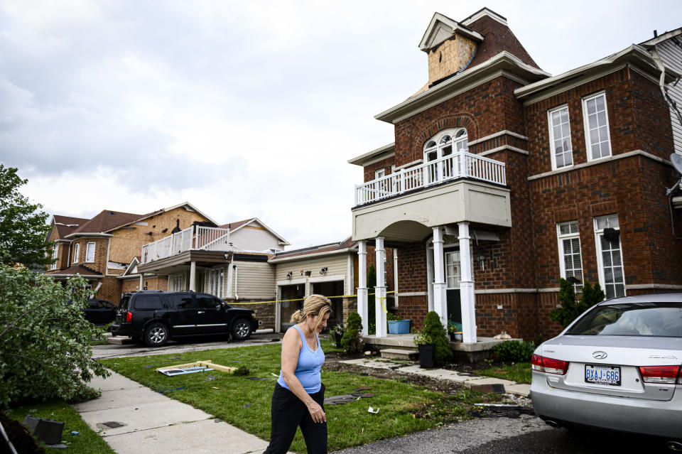 <p>A woman walks past damage caused by a tornado, in Barrie, Ont., on Thursday, July 15, 2021. THE CANADIAN PRESS/Christopher Katsarov</p>