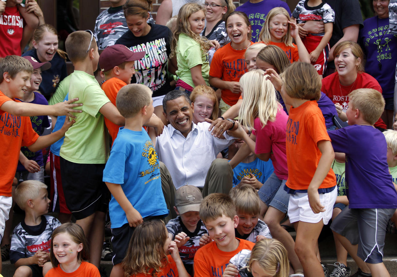 Children from public schools in the town of Chatfield, Minnesota, help U.S. President Barack Obama get up after he posed with them for a picture, during his bus trip to the Midwest August 15, 2011. Obama blasted Republicans over taxes on Monday as he launched a bus tour of the U.S. Midwest to tout his job-growth strategy and distance himself from anger toward Washington that could dent his 2012 re-election hopes. Obama is traveling on a bus tour through Minnesota, Iowa and Illinois.     REUTERS/Jason Reed   (UNITED STATES - Tags: POLITICS EDUCATION IMAGES OF THE DAY PROFILE)