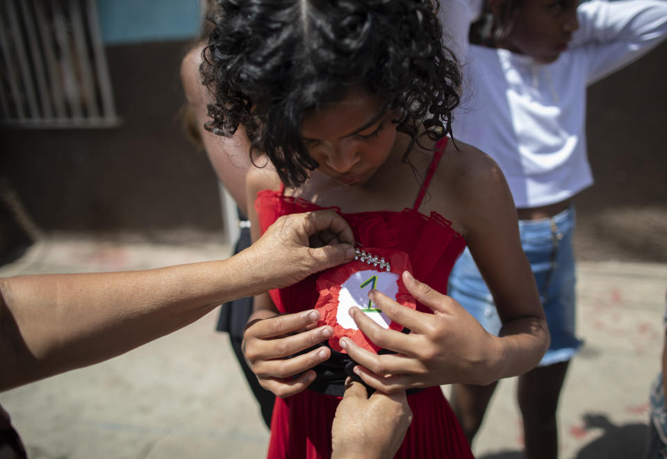 An organizer pins a #1 badge on Rosario Gutierrez, 11, after she was selected as child queen for the upcoming carnival festivities during a homespun beauty pageant, in the Antimano neighborhood of Caracas, Venezuela, Friday, Feb. 5, 2021. Neighborhood organizers said they're trying to revive this carnival pageant tradition that's been lost in recent years of economic and political crisis. (AP Photo/Ariana Cubillos)