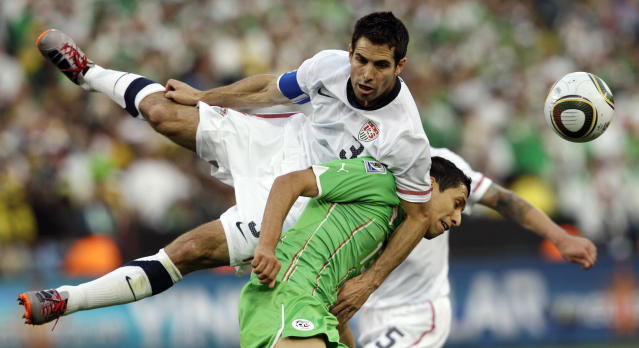 """FILE - In this June 23, 2010, file photo, Algeria's Karim Matmour, bottom, competes for the ball with United States' Carlos Bocanegra during a World Cup soccer game in Pretoria, South Africa. Bocanegra will retire at the conclusion of Chivas USA's season, ending the stalwart defender's 15-year pro soccer career. The 35-year-old Bocanegra announced his decision Thursday, Sept. 4, 2014. Last-place Chivas USA's regular season ends Oct. 26. """"I'm still hungry for the game, and I want to play, but unfortunately you can't play forever,"""" Bocanegra said. (AP Photo/Elise Amendola, File)"""