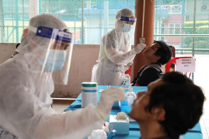 FILE PHOTO: Medical workers collect swab samples from people at a coronavirus disease (COVID-19) testing centre, in Petaling Jaya