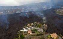 Lava from a volcano eruption flows destroying houses on the island of La Palma in the Canaries, Spain, Tuesday, Sept. 21, 2021. A dormant volcano on a small Spanish island in the Atlantic Ocean erupted on Sunday, forcing the evacuation of thousands of people. Huge plumes of black-and-white smoke shot out from a volcanic ridge where scientists had been monitoring the accumulation of molten lava below the surface. (AP Photo/Emilio Morenatti)