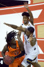 Oklahoma State's Isaac Likekele (13) looks to pass under pressure from West Virginia's Taz Sherman, back, and Gabe Osabuohien (3) during the first half of an NCAA college basketball game in the second round of the Big 12 Conference tournament in Kansas City, Mo., Thursday, March 11, 2021. (AP Photo/Charlie Riedel)