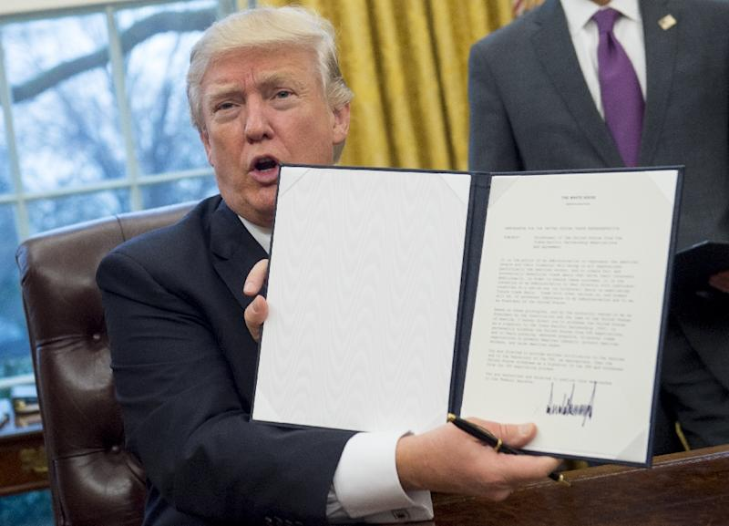 US President Donald Trump holds up an executive order withdrawing the US from the Trans-Pacific Partnership after signing it in the Oval Office of the White House on January 23, 2017 (AFP Photo/SAUL LOEB)