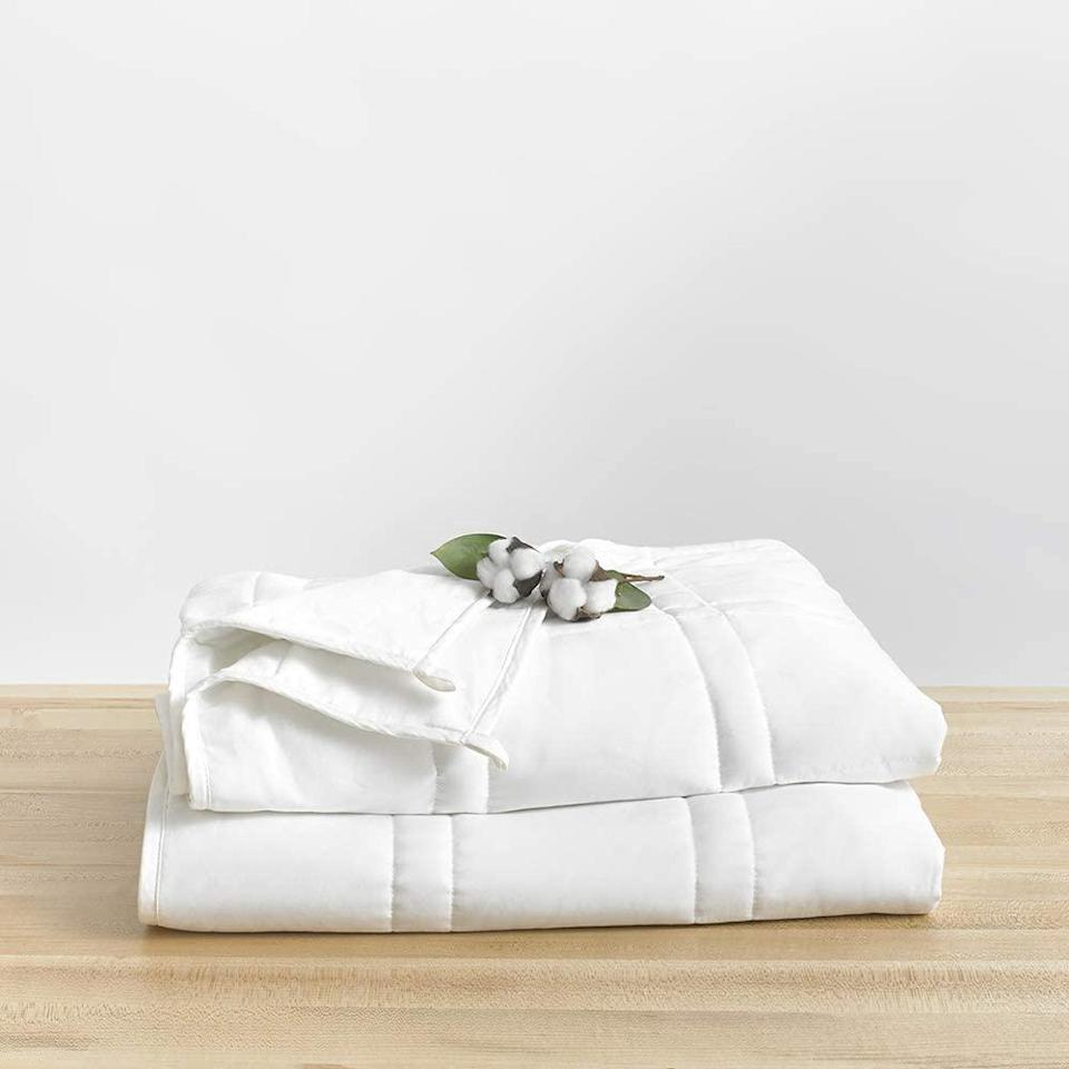 """Sleeping in is likely top priority once school wraps. Upgrade your graduate's sleep game with Baloo's Cool Cotton Weighted Blanket, which gently molds to the shape of your body. The idea is that the weighted filling simulates the feeling of a hug, which is thought to have therapeutic benefits. Made of 100 percent cotton, it's soft, breathable, and won't trap heat, so there's no worrying about sweating or getting too hot <a href=""""https://www.allure.com/story/covid-19-sleep-routine-tips-dreams?mbid=synd_yahoo_rss"""" rel=""""nofollow noopener"""" target=""""_blank"""" data-ylk=""""slk:while sleeping"""" class=""""link rapid-noclick-resp"""">while sleeping</a>."""