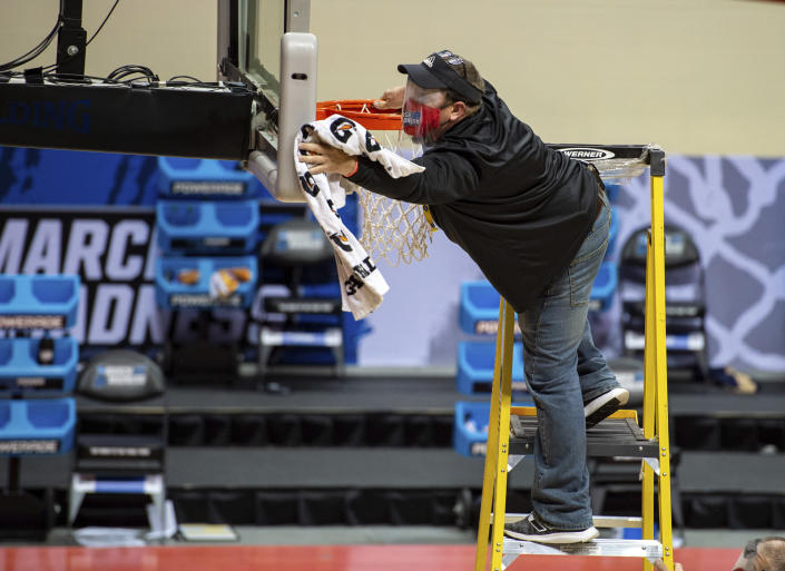 A worker cleans the backboard and rim on the court during halftime of a First Four game between Texas Southern and Mount St. Mary's in the NCAA men's college basketball tournament Thursday, March 18, 2021, in Bloomington, Ind. (AP Photo/Doug McSchooler)