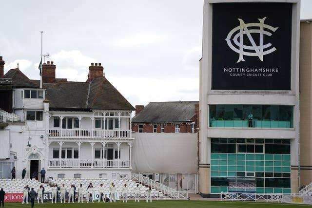 Durham players stand for a minute's silence as the flag is flown at half mast at Trent Bridge